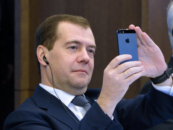 Russian Prime minister Dmitry Medvedev takes a picture of the Eiffel Tower with his smartphone during a meeting, on November 27, 2012, at French employers association MEDEF's headquarters in Paris. (Photo credi:ERIC FEFERBERG/AFP/Getty Images)