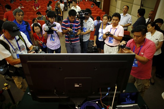 Journalists take pictures and videos of a screen displaying a court's microblog page during Bo Xilai's trial on August 23, 2013.