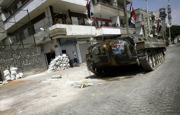 A Syrian armored personnel carrier takes position in Homs. (JOSEPH EID/AFP/Getty Images)