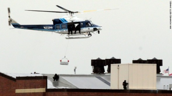 A Park Police helicopter hovers above snipers on the roof of a building at the Navy Yard complex Monday.