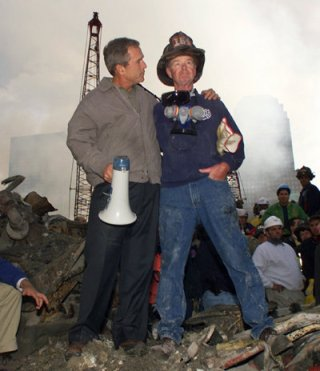 President George W. Bush embraces firefighter Bob Beckwith while standing in front of the collapsed World Trade Center