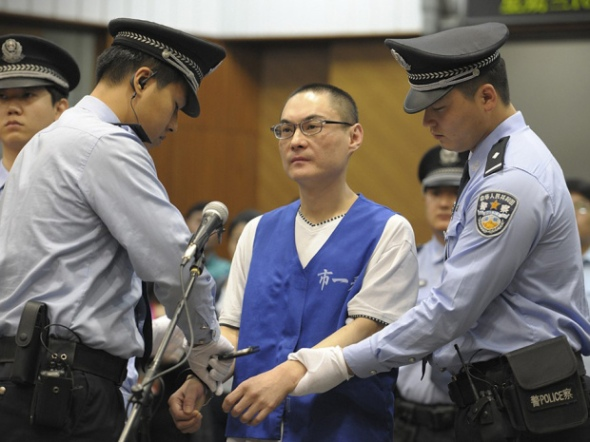 Han Lei, center, is handcuffed by police officers after his verdict was read in a court in Beijing, China Wednesday, Sept. 25, 2013. The court convicted Han and sentenced him to death for hurling a toddler to the ground in a case that horrified the Chinese public.