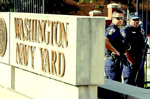 A Washington, D.C., Metro police officer (left) and a Washington Naval District policeman (right) stand guard at the main gate of the Washington Navy Yard on September 17, 2013. (Jason Reed/Reuters