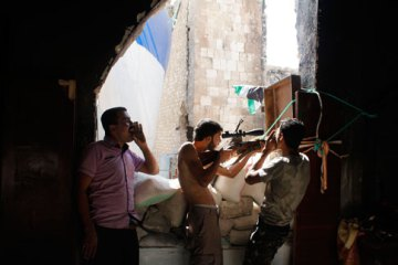 Molhem Barakat / Reuters Free Syrian Army fighters call out to forces loyal to Syria's President Bashar Assad, urging them to defect, as another fighter stands guard in the old city of Aleppo on Sept. 1, 2013