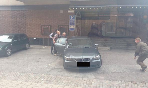 Bodyguards rush Vilks into his car.