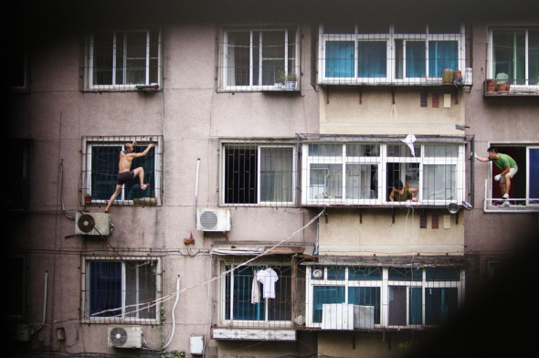 A man, whose last name is Hou (left), climbs outside a window with a knife, as his mother (ceter) and a plainclothes policeman look on, in Anshan, Liaoning province, on August 26, 2013. Hou held his mother captive in his apartment before climbing out of the window and threatening to cut himself. After several hours, he was captured by policemen who managed to enter the house from another window with the help of his mother, local media reported. (Reuters/Stringer)