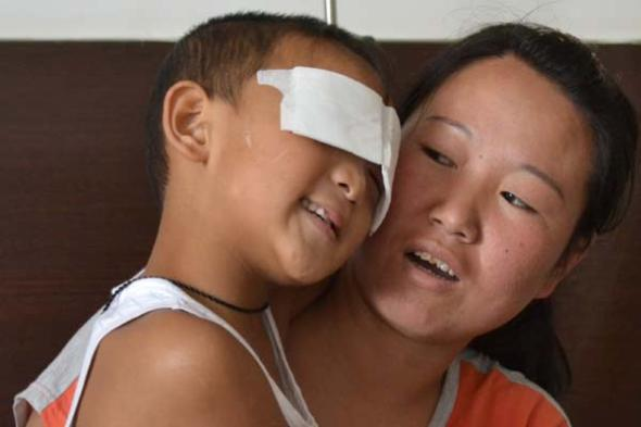 In his mother's arms, 6-year-old Guo Bin, whose eyes were gouged out by a woman last week, thanks a man who donated money to him in a hospital in Taiyuan,Shanxi province, on Tuesday. Police identified the boy's aunt, who has committed suicide, as the suspect, though doubts remain. [Hou Liqiang / China Daily]