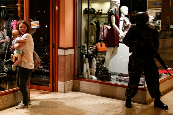 A woman shields a baby as a soldier stands guard inside the Westgate shopping mall after a shootout in Nairobi, on Sept. 21, 2013. Kabir Dhanji / EPA