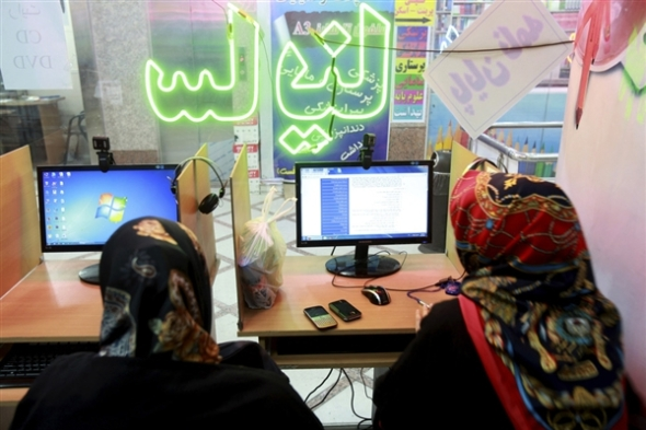 Two Iranian women surf the Internet at a cafe in Tehran, Iran, in September, when authorities briefly lifted blocks on social networks and then restored them. Ebrahim Noroozi / AP file