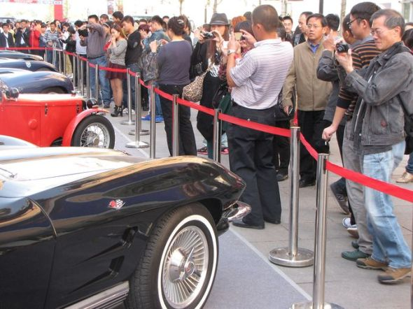 People photograph a display of classic automobiles, including a 1964 Chevrolet Corvette Stingray. (Photo: Calum MacLeod, USA TODAY)