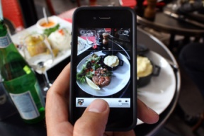 A man takes a picture with his mobile of foods in his plate as he is having lunch on July 19, 2012 in Paris.  AFP PHOTO / ANA AREVALO        (Photo credit should read ANA AREVALO/AFP/GettyImages)