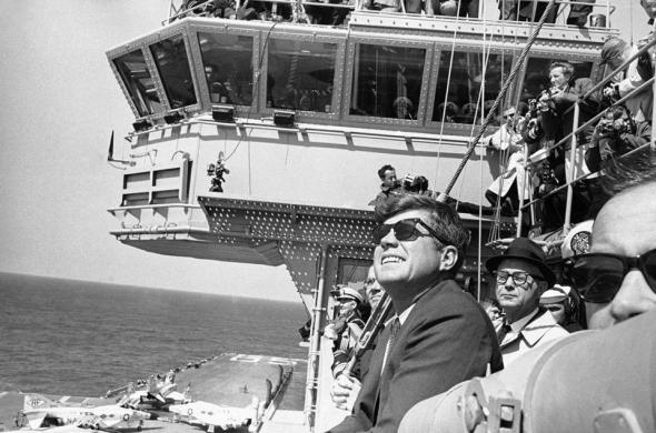 President John. F. Kennedy looks into the sky as planes from the Carrier Enterprise maneuver in a demonstration off the east coast on April 14, 1962. FILE 1962/ASSOCIATED PRESS
