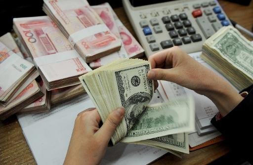 A teller counts US dollars and Chinese 100-yuan notes at a bank in Hefei, east China's Anhui province on January 16, 2011