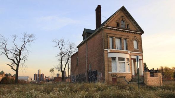 FILE - This Oct. 24, 2012 file photo shows a graffiti-marked abandoned home north of downtown Detroit, in background.(AP Photo)