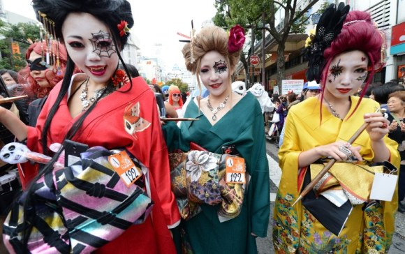 Women clad in special costumes pose for pictures as they walk on the street during the Halloween Parade in Kawasaki, suburb of Tokyo on October 28, 2012. Some 100,000 visitors enjoy the costume parade which about 3,000 people took part in.    AFP PHOTO/Toru YAMANAKA