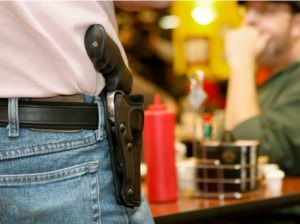 Bryan Hull, founding director of the Oklahoma Open Carry Association (OKOCA), wears an unconcealed side arm as he addresses OKOCA members gathered at Beverly's Pancake House in Oklahoma City