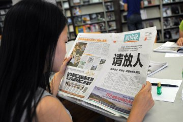 "A woman reads the New Express newspaper that on October 23, 2013 carried a full-page editorial with headline ""Please release our man"", in a library in Guangzhou, south China's Guangdong province. AFP / Getty Images"