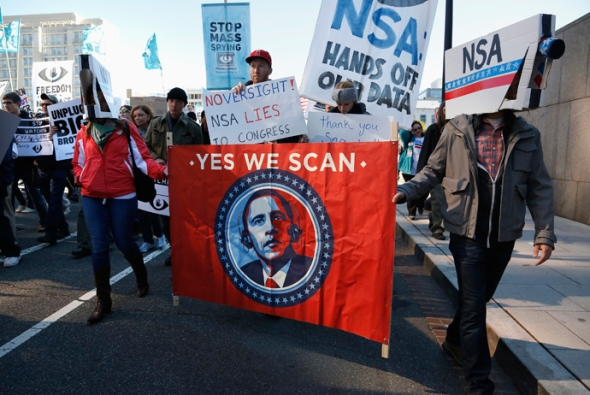 "Demonstrators wearing cardboard surveillance camera hats carry a sign depicting U.S. President Barack Obama at the ""Stop Watching Us: A Rally Against Mass Surveillance"" march in Washington, October 26, 2013. (Reuters / Jonathan Ernst)"