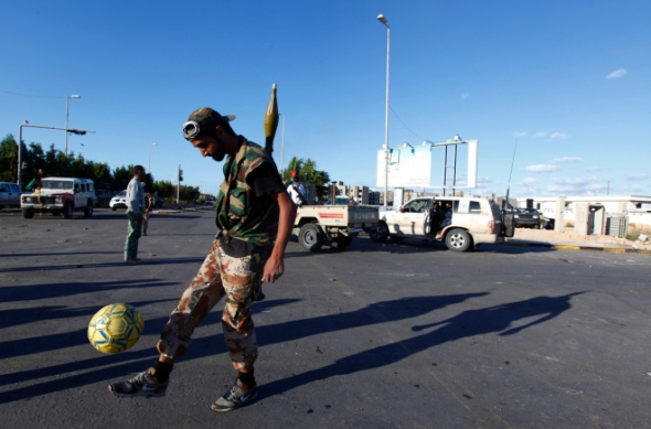 A rebel fighter loyal to Libya's interim government kicks a football as a battle rages nearby in Sirte October 12, 2011. Anis Mili / Reuters