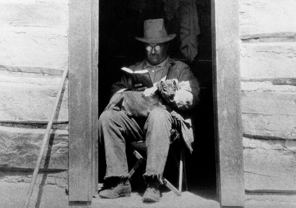 President Theodore Roosevelt, considered one of the most well-read American politicians of all time, reads a book with his dog Skij on his lap in Colorado in April 1905. (AP)