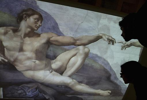 "Museum staff at the British Museum looking up at a projection of Michelangelo's ""Creation of Adam"". Photo: Getty"