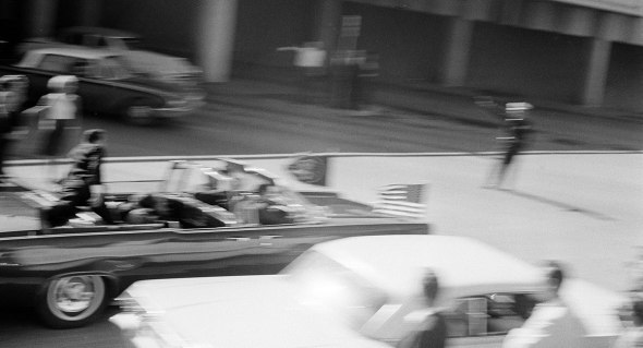 resident Kennedy's limousine speeds along Elm Street toward the Stemmons Freeway overpass moments after he was shot at Dealey Plaza in Dallas, Tex., Nov. 22, 1963. Secret Service agent Clint Hill is seen on the back of the car as Jacqueline Kennedy tends to her fatally wounded husband. (AP Photo)