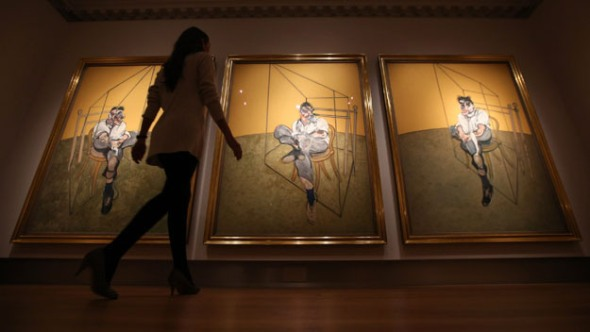 "A member of Christie's staff walks towards Francis Bacon's ""Three Studies of Lucien Freud"" on Oct. 14, 2013 in London, England. (credit: Getty Images)"
