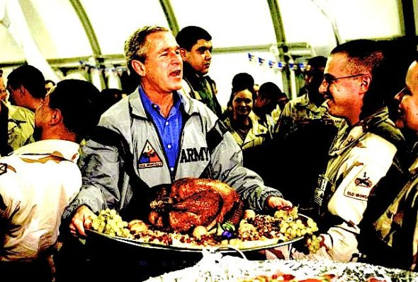 President George W. Bush carries a platter with a cooked turkey during a visit to troops serving in Iraq in 2003. (ASSOCIATED PRESS) Photo by: ANJA NIEDRINGHAUS