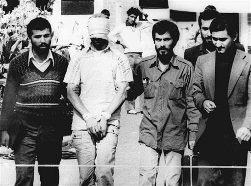 FILE - In this Nov. 9, 1979, file photo, one of the hostages being held at the U.S. Embassy in Tehran is displayed to the crowd, blindfolded and with his hands bound, outside the embassy. Fifty-two of the hostages endured 444 days of captivity. Former Iranian hostages had varied reactions to the news of the nuclear deal between the U.S. and Iran in what is being billed as a trust-building agreement designed to yield a more comprehensive deal six months from now. (AP Photo/File)