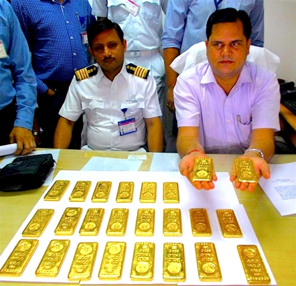 A customs officer (right) shows 24 gold bars to the media after it was seized at the Netaji Subhash Chandra Bose International Airport in Kolkata, India, on Wednesday.