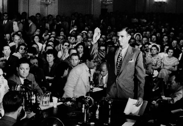 Alger Hiss, accused of Communist espionage, takes an oath during hearings before the House Committee on Un-American Activities.  He denied Whittaker Chambers' accusation that he was a Communist. --- Image by © Bettmann/CORBIS