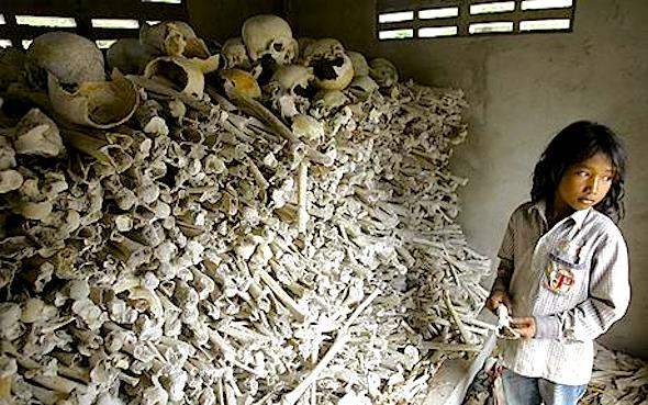 "Meo Soknen...Cambodian Meo Soknen, 13, stands inside a small shrine full of human bones and skulls, all victims of the Khmer Rouge,  near her home Tuesday, March 31, 2009, in the Kandal Steung district of Kandal province, Cambodia.  Kaing Guek Eav, also know as ""Duch"", the commander of the infamous Toul Sleng prison, accepted responsibility Tuesday during the second day of a UN-backed tribual for torturing and executing thousands of inmates at Toul Sleng.  The small shrine, located 27 kilometers, (17 miles) south of Phnom Penh is one of many out of the way and forgotten monuments to the ""Killing Fields.""  (AP Photo/Heng Sinith)"