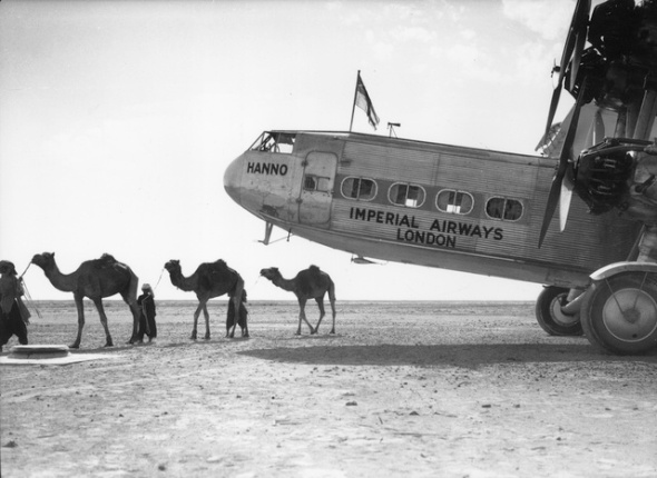 April 1934:  A line of camels is led past the Imperial Airways liner 'Hanno' at Gwadar in Muscat, the capital of Oman.  (Photo by Fox Photos/Getty Images)
