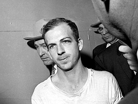 In this Nov. 23, 1963 file photo, Lee Harvey Oswald is led down a corridor of the Dallas police station for another round of questioning in connection with the assassination of U.S, President John F. Kennedy. Oswald, who denied any involvement in the shooting, was formally charged with murder. (AP Photo)
