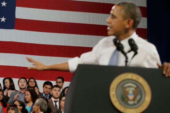 President Barack Obama attempts to respond to Ju Hong (lower left), who began to heckle him about anti-deportation policies Monday at the Betty Ann Ong Chinese Recreation Center in San Francisco. Pablo Martinez Monsivais/AP