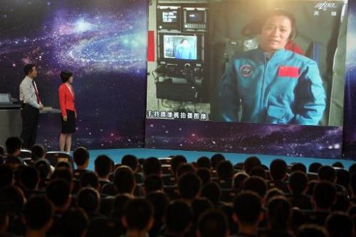 Chinese astrounaut, mission commander Nie Haisheng, speaks to students via video link, gathered at a school in Beijing, of June 20, 2013