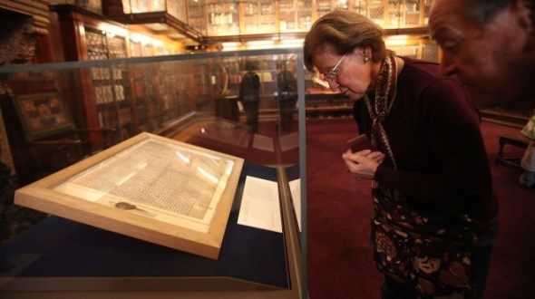 Visitors look at one of the earliest original manuscripts of the Magna Cart. (credit: Mario Tama/Getty Images)