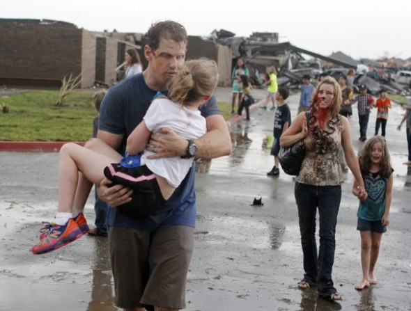 Teachers carry children away from Briarwood Elementary School after a tornado destroyed the school in south Oklahoma City. (Paul Hellstern/Associated Press)