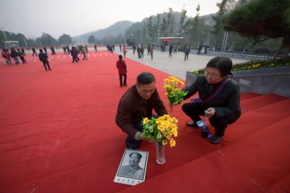 WANG ZHAO/AFP/Getty Images - A man and a woman prepare to present flowers to a bronze statue of former Chinese leader Mao Zedong at a square in Shaoshan, in China's Hunan province, on Dec. 24.