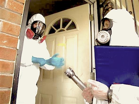 certified industrial hygienist Gary Siebenschuh, left, and assistant Courtney Van Stolk preparing to enter a house that was once used as a clandestine methamphetamine lab in Memphis, Tenn. The house was placed under quarantine after a Nov. 6 fire that police said was caused by a meth lab that exploded in the attic of the house. Siebenschuh and Van Stolk were hired by the homeowner to test the home for meth residue. (AP Photo/Adrian Sainz).