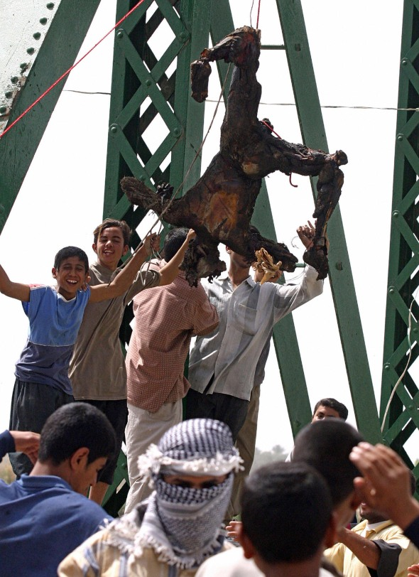 Iraqis chant anti-American slogans as a charred boy hangs from a bridge over the Euphrates river in Fallujah.Photo: Getty Images