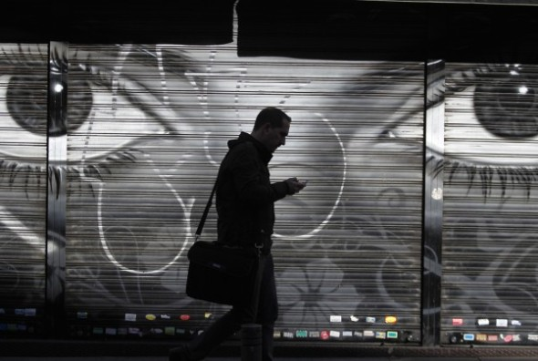 Francisco Seco/AP - In this October 2013 file photo, a man looks at his cellphone as he walks on the street in downtown Madrid. The NSA's ability to crack cellphone encryption used by the majority of cellphones in the world offers it wide-ranging powers to listen in on private conversations.