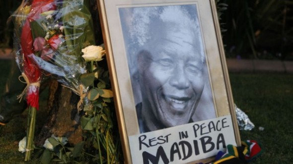 A framed portrait of former president Nelson Mandela and flowers are placed outside Mandela's Johannesburg home Friday, December 6, 2013. (photo credit: AP/Denis Farrell)