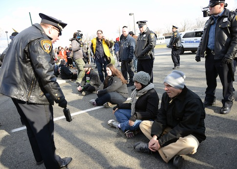 A police offer speaks to protesters outside of the Walmart department store after they blocked traffic in Secaucus, N.J., on Friday, Nov. 29, 2013.  The activists rallied to protest the wages paid to Walmart workers and to urge the company to improve labor standards. (AP Photo/The Jersey Journal,  Reena Rose Sibayan)
