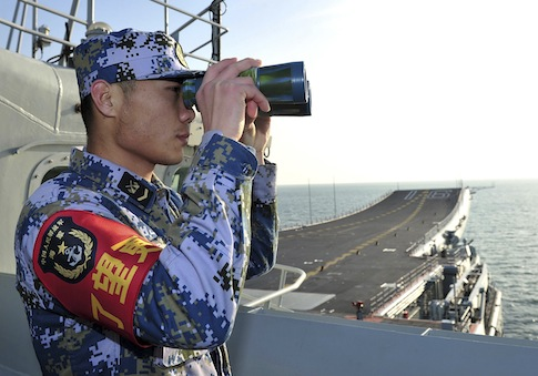 In this Tuesday, Nov. 26, 2013 photo, a crew member of Chinese People's Liberation Army (PLA) Navy monitors on the deck of the China's aircraft carrier, the Liaoning, sailing on the East China Sea for sea trials. The Liaoning departed for its first-ever sea trials in the South China Sea, a mission likely to draw scrutiny amid Beijing's drive to assert its claims to those waters and their island groups. (AP Photo) CHINA OUT