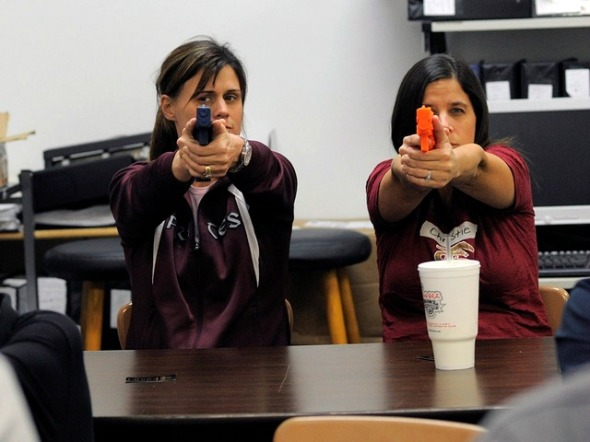 A group of local public school teachers from nearby schools use rubber training guns as they practice proper firearms handling during a teachers-only firearms training class offered for free at the Veritas Training Academy in Sarasota, Florida January 11, 2013. The December 14 tragedy in Newtown, Connecticut, where 20 first-graders and six adults were killed at Sandy Hook Elementary School, has sparked a national debate about whether to arm teachers, prompting passionate arguments on both sides. REUTERS/Brian Blanco (UNITED STATES - Tags: SOCIETY POLITICS EDUCATION)