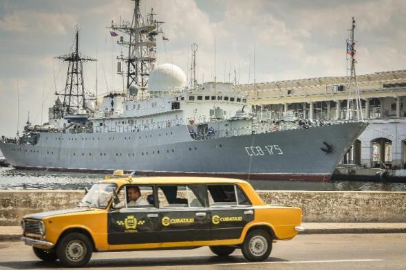 A Soviet-made Lada limousine passes by Russian Vishnya (also known as Meridian) class warship CCB-175 Viktor Leonov, docked, on February 26, 2014, at Havana harbor (AFP Photo/Adalberto Roque)