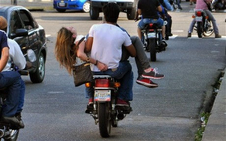 Genesis Carmona is carried away by motorcycle, after being shot in the head (Photo: EPA)