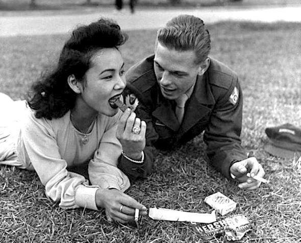 A soldier and a local girl share a chocolate bar and cigarettes, 1946.