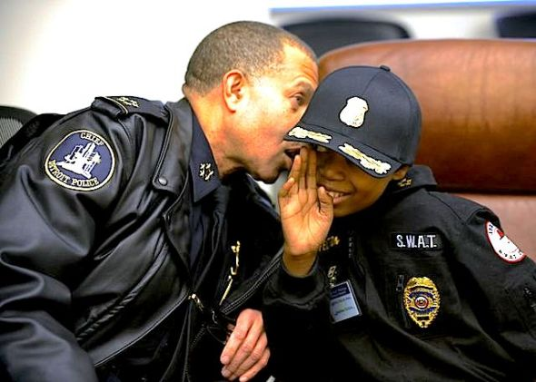 Detroit Police Chief James Craig whispers in the ear of Jayvon Felton, 9, after Felton was named Chief for A Day by Craig, at Detroit Public Safety Headquarters in Detroit on Friday Jan. 31, 2014. Felton, 9, was diagnosed with acute lymphoblastic leukemia in April. (AP Photo/Detroit News, David Coates)